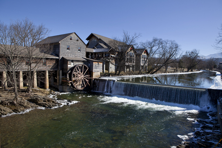 Watermill on the Little Pigeon river, in the mountain community of Pigeon Forge, Tennessee during the winter  Ice can be seen along the banks of the river Фото со стока