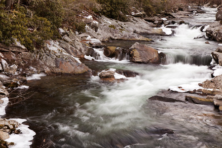Mountain stream flowing through ice covered rocks in Great Smoky Mountains National Park in the winter near Gatlinburg, Tennessee