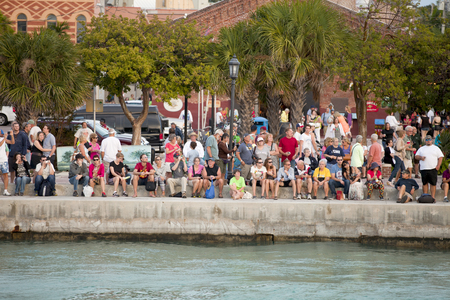 croud: Hundreds of tourists gathering at Mallory Square is a plaza located in the city of Key West, Florida, United States for the  Sunset Celebration  to watch the sunset over the Gulf of Mexico   Stock Photo
