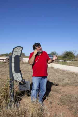 Man using landline telephone in the middle of nowhere in Texas  photo