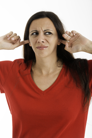 30 s: Woman with fingers in ears upset about the noise, Shot on a white background  Not Lisining