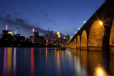 A famosa Ponte de pedra do arco, ao anoitecer, com reflexos no rio Mississippi em Minneapolis, Minnesota