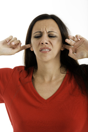 30 s: Woman with fingers in ears upset about the noise, Shot on a white background  not lisining Stock Photo
