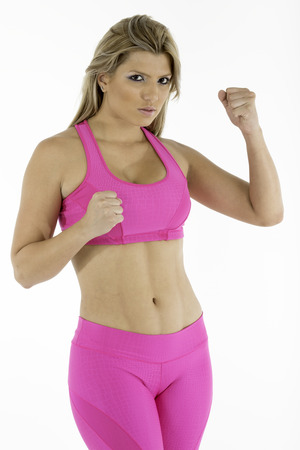 tough: Fitness instructor in hot pink workout outfit working out  White background
