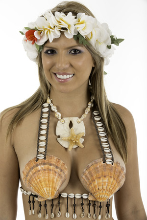 hawaiian lei: Pretty woman dressed in Hawaiian costume made of sea shells and wearing a lei  looking at camera smiling shot on white background  Stock Photo