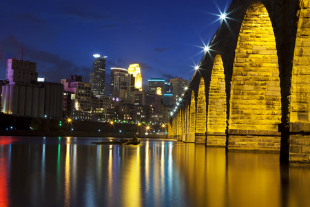 The famous Stone Arch Bridge at dusk with reflections in the Mississippi river in Minneapolis, Minnesota  스톡 콘텐츠