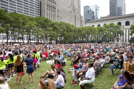 People enjoing a concert in Bryant Park at 6th Ave between 40th and 42nd Street in midtown Manhattan . The New York Public Library is in the background.