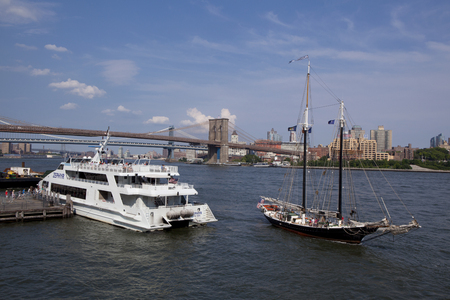 tour boats: Two different types of tour boats at the seaport over the East River in Lower Manhattan, New York City with the Brooklyn and Manhattan Bridge in the background. Editorial