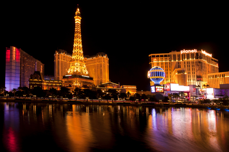 Nightlife along the Las Vegas Strip with Bally\'s, Paris and Planet Hollywood Casinos reflecting in the Bellagio lake . Picture shows the Paris balloon and the Eiffel Tower replica which is about half the size of the original in France Time exposure shows
