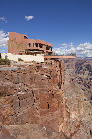 Tourist enjoying the view of the west rim of The Grand Canyon from the Skywalk. This transparent floor, horseshoe-shaped cantilever bridge gives people an amazing view of the Grand Canyon Western Rim and the Colorado River below. The skywalk is between 50