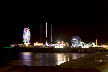 Steel Pier amusement pier extends over the beach and ocean in Atlantic City and is located opposite the Boardwalk from Trump Taj Mahal Casino. Night shot with long exposure for motion blur effect on rides. 新闻类图片