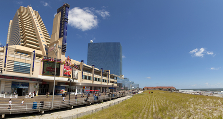 showboat: The Showboat Casino with the Revel Casino behind it in Atlantic City, New Jersey. Both of the Casinos will be closing in September of 2014 due to economic downturn in the comunity. People walking on the boardwalk.