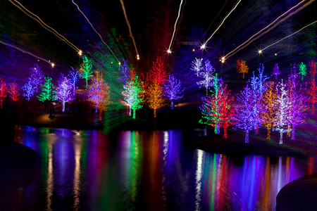 light streaks: Abstract of trees tightly wrapped in LED lights for the Christmas holidays reflecting in lake. Each tree is wrapped in one color.  Camera zoom use to produce light streaks on long exposure Stock Photo