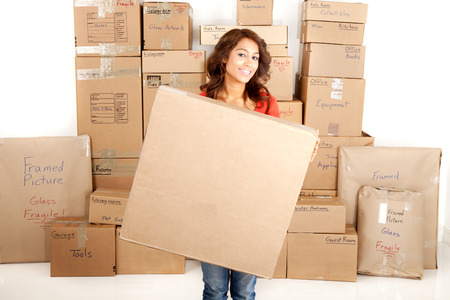 labeled: Yong woman moving holding a blank box with boxes stacked in the background Stock Photo