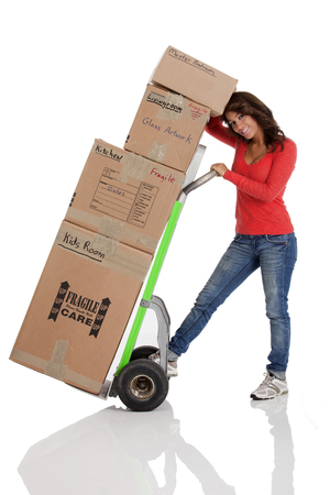 dolly: Young woman moving boxs with with a habd truck or dolly. Shot on a white background Stock Photo