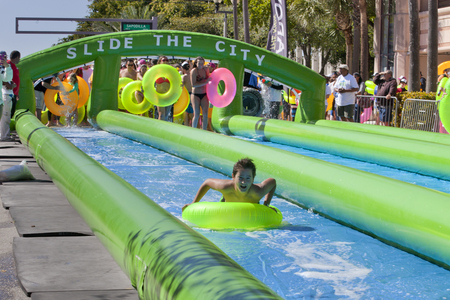 A 1000 foot long water slide is set up on Clematis Street in downtown West Palm Beach, Florida. The giagantic water slide was enjoyed by thousands of people using brightly colored swimming tubes and different inflatable pool toys. Slide the City Event Editorial