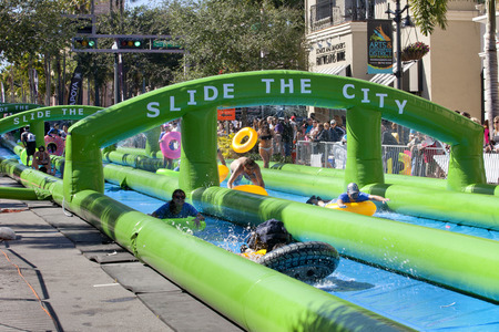 inter: A 1000 foot long water slide is set up on Clematis Street in downtown West Palm Beach, Florida. The giagantic water slide was enjoyed by thousands of people using brightly colored swimming tubes and different inflatable pool toys. Slide the City Event Editorial
