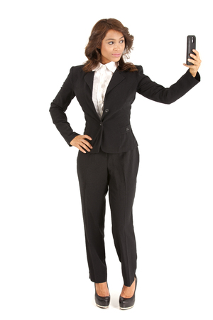 celphone: Young business woman using a celphone to take a selfie