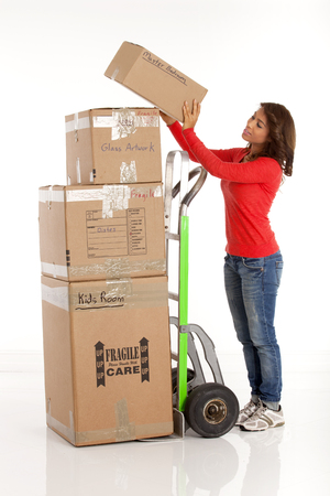 hand cart: Young woman moving a stack of boxes with a hand cart