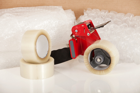 packing material: Tape dispenser, bubble wrap and packing tape shot on a white background