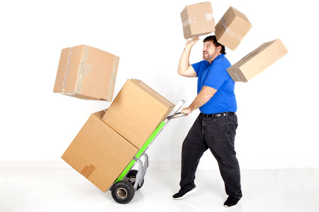 domestic life: moving,accident,dropping,falling,box,hand truck,dolly,boxes,packing,cardboard box,clothing,moving box,cardboard,holding,blank,stacked,labeled,moving house,home interior,package,domestic life,carrying,carton,indoors,label,stack,standing,lifting,room,white,