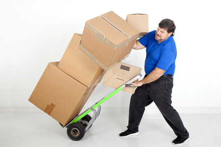 hand move: Man dropping boxes off of a hand cart while trying to move them Stock Photo