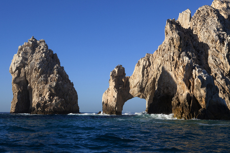 natural arch: Ocean waves splashing on the famous natural arch at Lands End in Cabo San Lucas Mexico