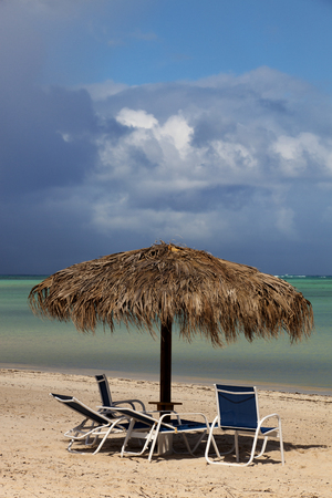 palapa: Empty beach retreat overlooking the ocean with approching storm in the background.