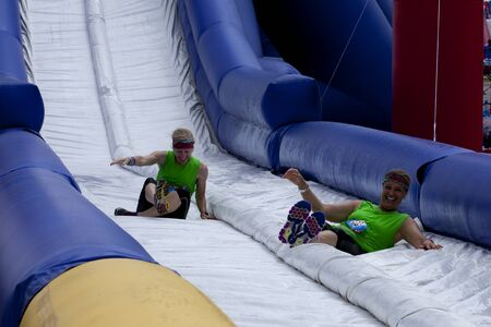 Friends sliding happy endings waterslide obstacle at the finish of the Wipeout 5K Run obstacles course in Wilmington Delaware  The Wipeout Run is themed after the popular ABC game show Wipeout and has12 obstacles. Some of the obstacles incorporated in