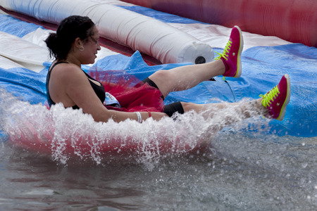 Woman splashes into the bottom of the tumble tubes water slide obstacle at the Wipeout 5K Run obstacles course in Wilmington Delaware  The Wipeout Run is themed after the popular ABC game show Wipeout and has12 obstacles. Some of the obstacles incorpo Editorial