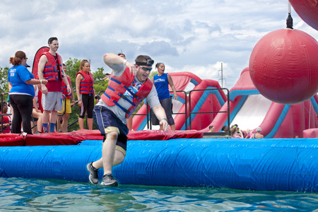 Man falling at the wrecking balls water obstacle at the Wipeout 5K Run obstacles course in Wilmington Delaware  The Wipeout Run is themed after the popular ABC game show Wipeout and has12 obstacles. Some of the obstacles incorporated in the course are