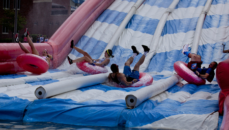 Friends splashes into the bottom of the tumble tubes water slide obstacle at the Wipeout 5K Run obstacles course in Wilmington Delaware  The Wipeout Run is themed after the popular ABC game show Wipeout and has12 obstacles. Some of the obstacles incor