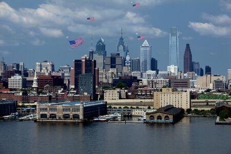 banderas america: Parashoot paracaidistas en el centro de Filadelfia Pensilvania con banderas americanas gigantes unidos a ellos para celebrar el Día de la Bandera