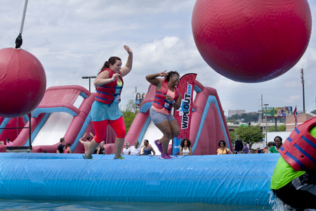 red ball: Woman falling at the wrecking balls water obstacle at the Wipeout 5K Run obstacles course in Wilmington Delaware  The Wipeout Run is themed after the popular ABC game show Wipeout and has12 obstacles. Some of the obstacles incorporated in the course a