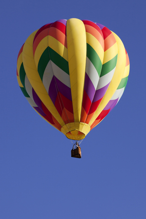 flight mode: Colorful hot air balloons as part of the mass ascension launch of over 100 colorful balloons at the New Jersey Ballooning Festival in Whitehouse Station, New Jersey during the early morning race. Stock Photo