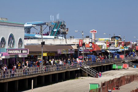 View of the famous Wildwood, New Jersey boardwalk filled with tourist enjoying a beautiful summer day