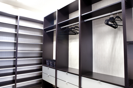 Large walk-in closet with empty shelves and draws Banco de Imagens