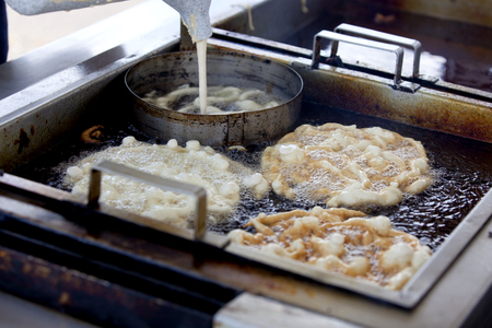 Inside the funnel cake booth, vendor is pouring funnelcake batter though a funnel into boiling hot oil to make a popular fairfestival dessert. Banco de Imagens