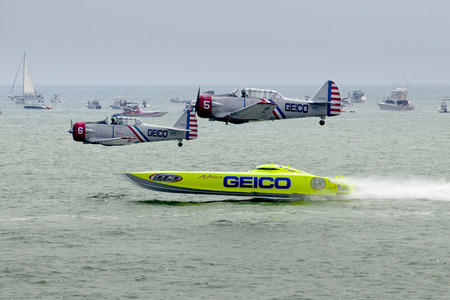 The Geico Skytypers flying preforming precision aerial maneuvers with the Miss Geico speedboat over the ocean at the Atlantic City Airshow in New Jersey on a hot hazy summer day. The Geico Skytypers fly in SNJ-2 World War II-era planes. Spectator boat