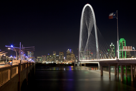 forground: Downtowwn Dallas, Texas at night with the Trinity River in the forground and the new Margaret Hunt Hill Bridge Editorial