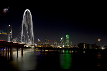 Downtown Dallas, Texas at night with the Trinity River in the foreground and the new Margaret Hunt Hill Bridge