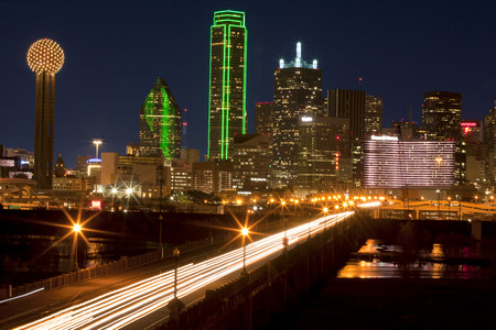 forground: Evening comute in downtowwn Dallas, Texas at night with the Trinity River in the forground