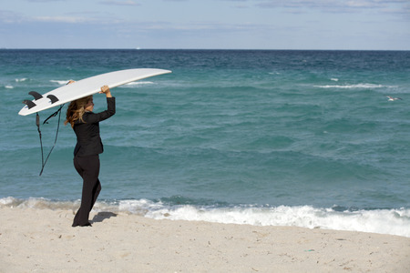 business metaphor: Business Metaphor: Working Vacation Beautiful business woman in business suit posing on a surfboard