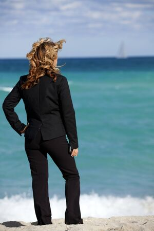 business metaphor: Business Metaphor: Working Vacation Beautiful business standing on the beach looking at the ocean. Sailboat in far background.