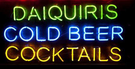 """Segno al neon Bar con le parole """"daiquiri, birra alla spina e cocktail"""" a luci al neon colorate su sfondo nero"""