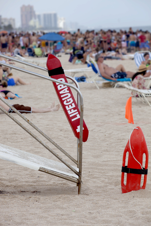 spring break: Modern lifeguard with lots of students in the background celebrating spring break in Fort Lauderdale, Florida