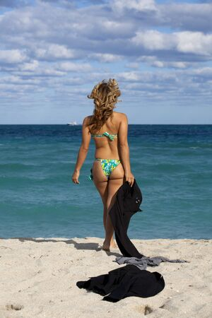 business metaphor: Business Metaphor: Working Vacation Beautiful business woman taking off business suit revealing a bikini on a tropical beach Stock Photo