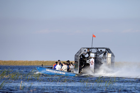 Tourist enjoying and airboat ecotour of the Sawgrass Recreation Park in the Everglades . Sawgrass airboat tours are one of south Floridas top destinations activities for visitors to the state.