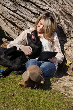 ser humano: Mujer joven que usa una tableta de ordenador que se sienta y que abraza a su perro labrador negro en Trinity Park en el centro de Fort Worth, Texas. Composición que muestra que el perro y el ser humano son dos mejores amigos. Espacio en blanco