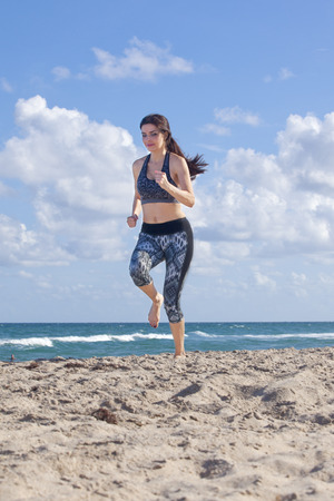 getting away from it all: Woman running on the beach barefooted Stock Photo